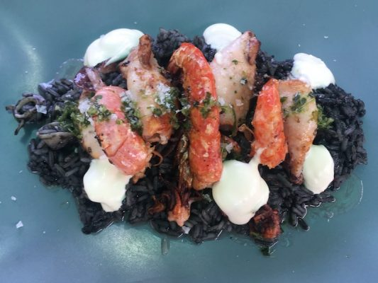 Shrimp & squid on a bed of black rice with aioli and herb garnish