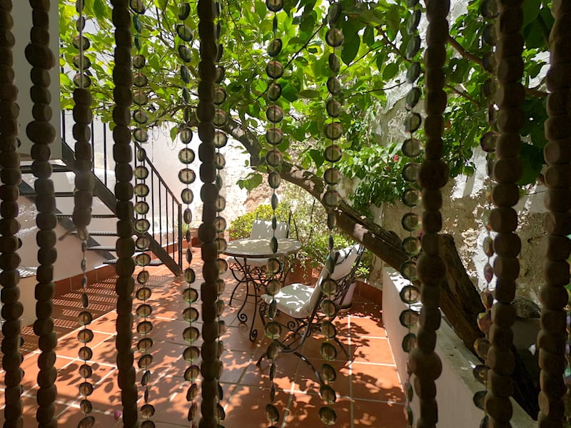 Lower Patio area at Lemon Tree Patio featuring terracotta tiles and overhanging lemon tree over the wrought iron table & chairs
