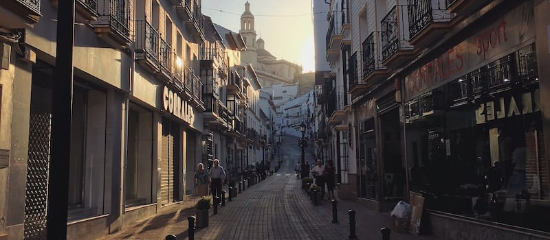 The Main narrow Street of olvera with the church poking out overlooking the town at sunset
