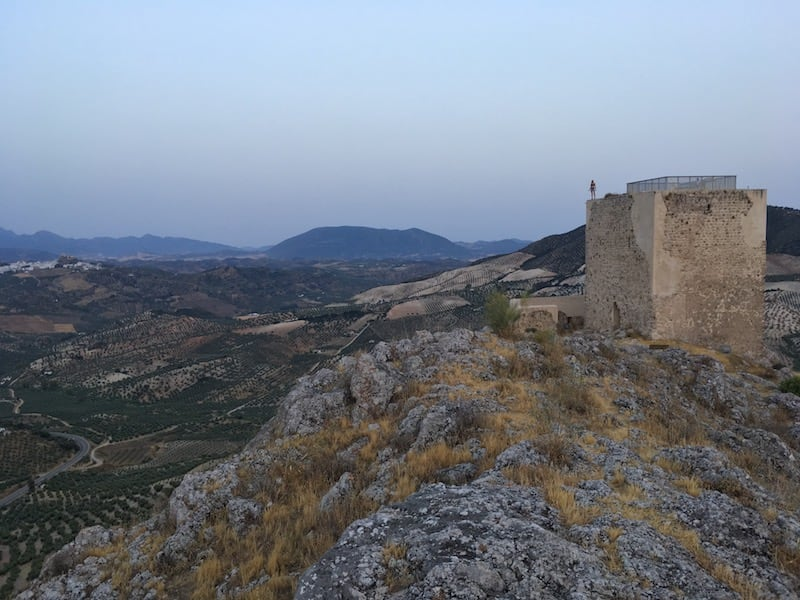 Figure stood on top of Castillo De Hierro looking out to Olvera at sunrise
